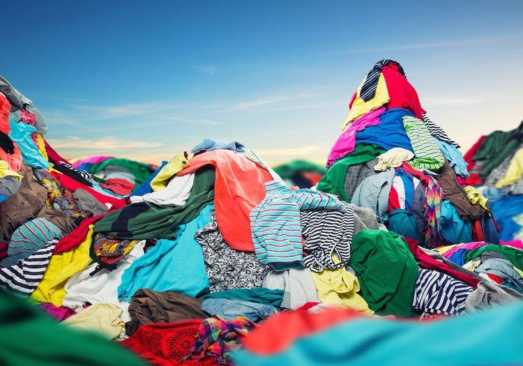 Big heap of colorful clothes on sky background. Textiel waste. Resíduos têxteis. Roupas para doação.