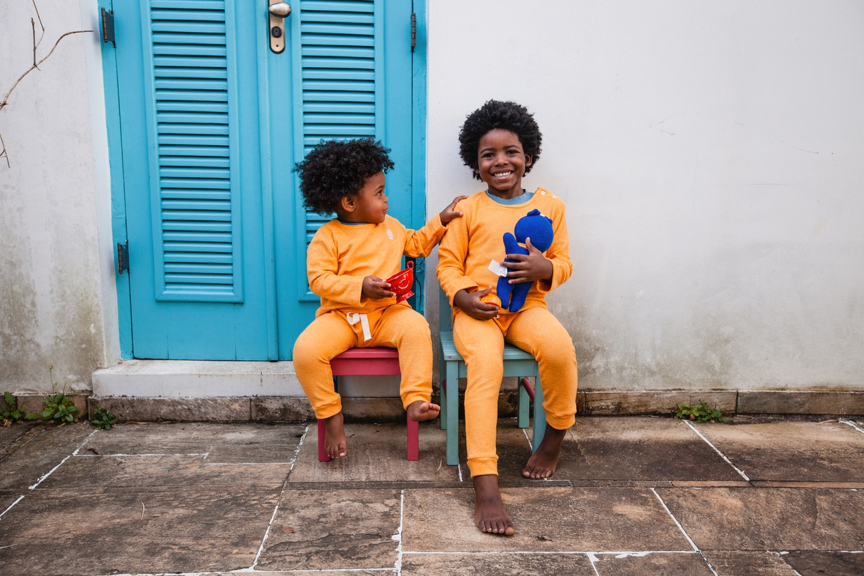 Studio Pipoca - moda infantil e sustentável. Crianças negras com vestuário infantil sustentável posam em frente a parede branca e porta azul, com brinquedos.